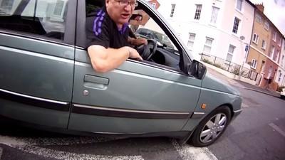Questo video dell'automobilista che si schianta di faccia mentre insegue un ciclista è un'opera d'arte