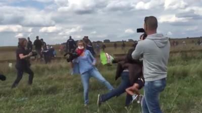 Eine Kamerafrau in Ungarn stellt einem fliehenden Mann mit Kind das Bein