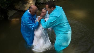 Botezul din România implică uneori albii de râu, butoaie imense şi bazine