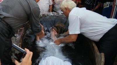 Foto's van volwassenen die worden gedoopt in rivieren en zwembaden