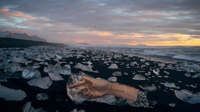 Een graffitikunstenaar beschildert afdrijvende ijsschotsen van een smeltende gletscher