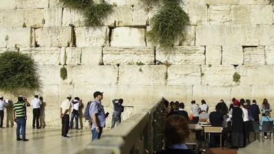 Fotos de hombres y mujeres rezando en partes separadas del Muro de las Lamentaciones