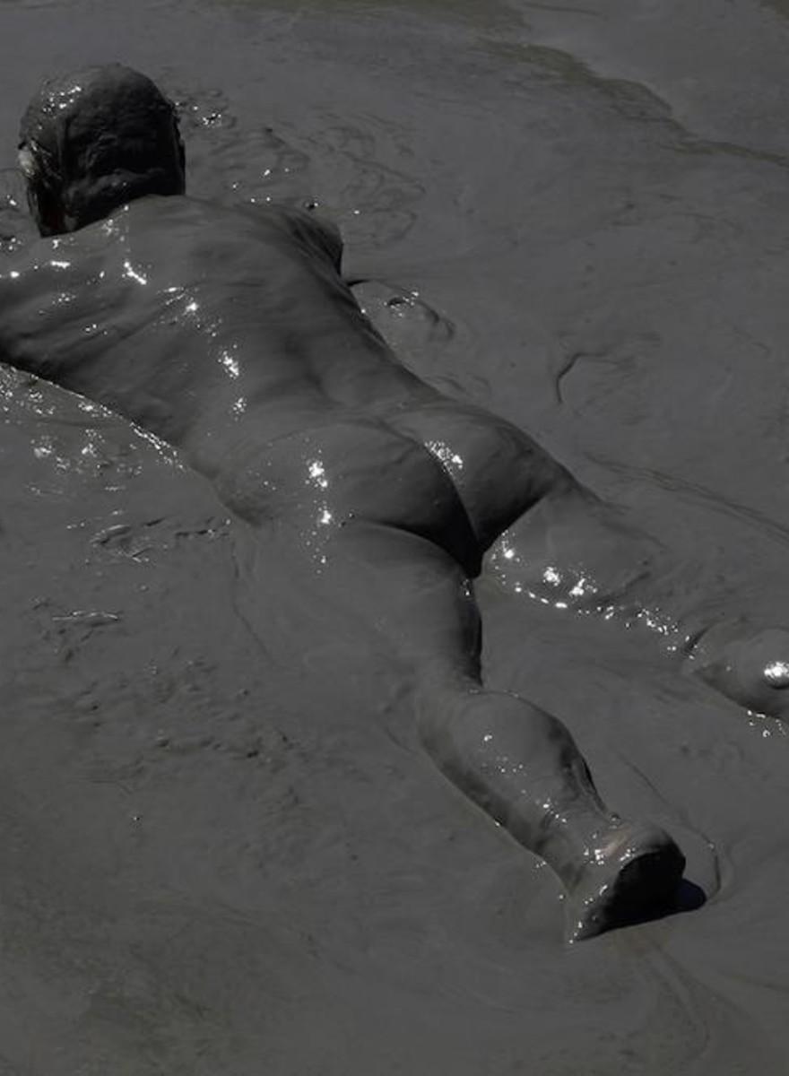 Foto's van naakte Grieken die een modderbad nemen