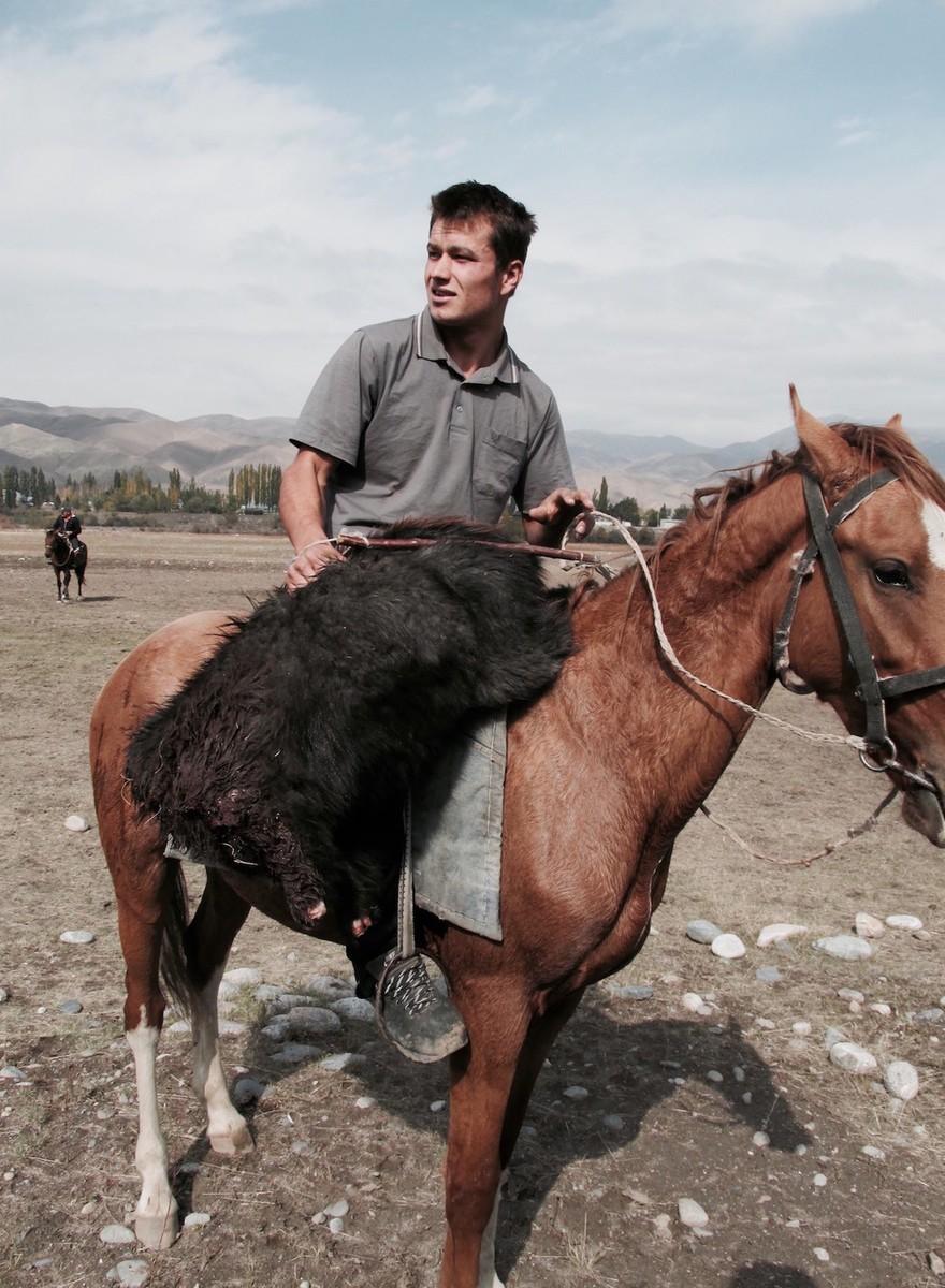 Foto's van dorpelingen die polo spelen met een dode geit in Kirgizië