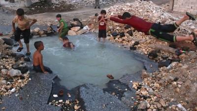 Assad promociona sus playas mientras los niños de Alepo nadan en los cráteres de los bombardeos