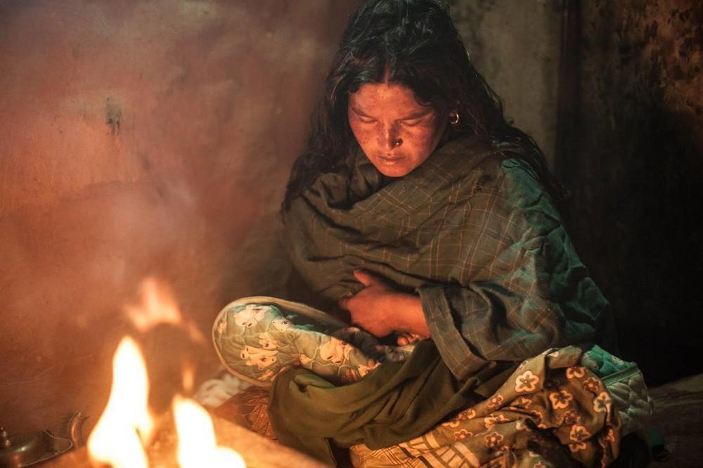 Η Laxmi ανάβει μια μικρή φωτιά   για να ζεσταθεί η ίδια και το μωρό της.