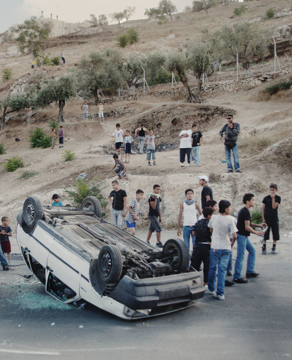 Some Palestinian boys admire their handiwork after flipping a broken car upside down during a demonstration in East Jerusalem, 2010.
