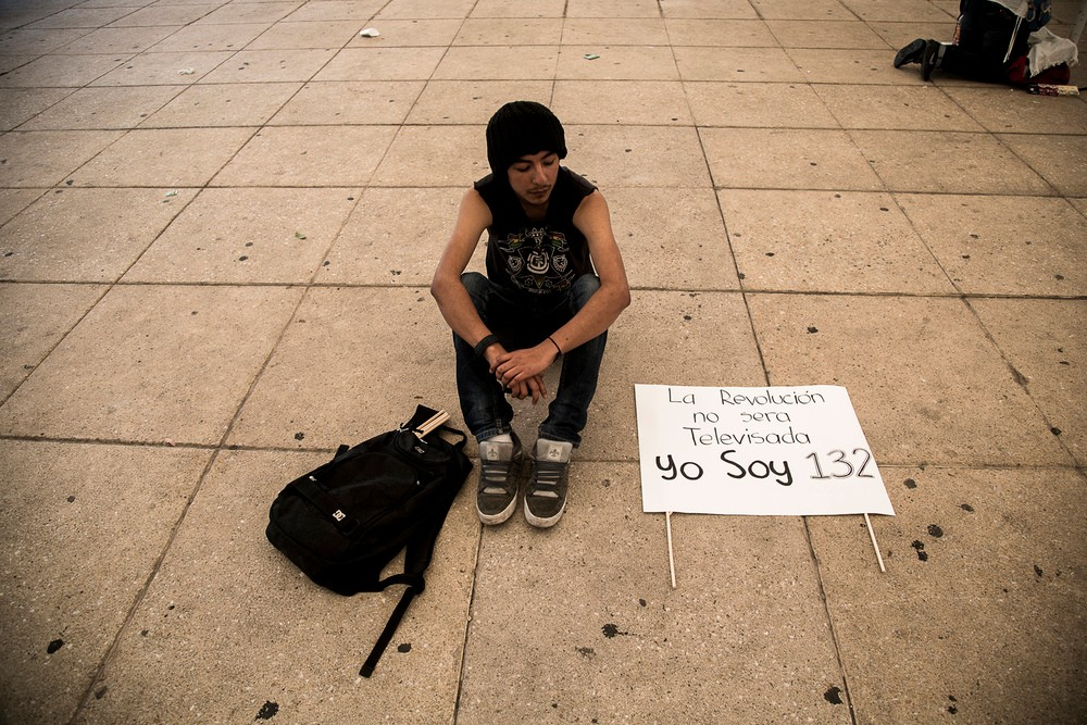 "A student member of the #YoSoy132  movement waits to march with a sign reading, ""The revolution will not be televised. #YoSoy132."""