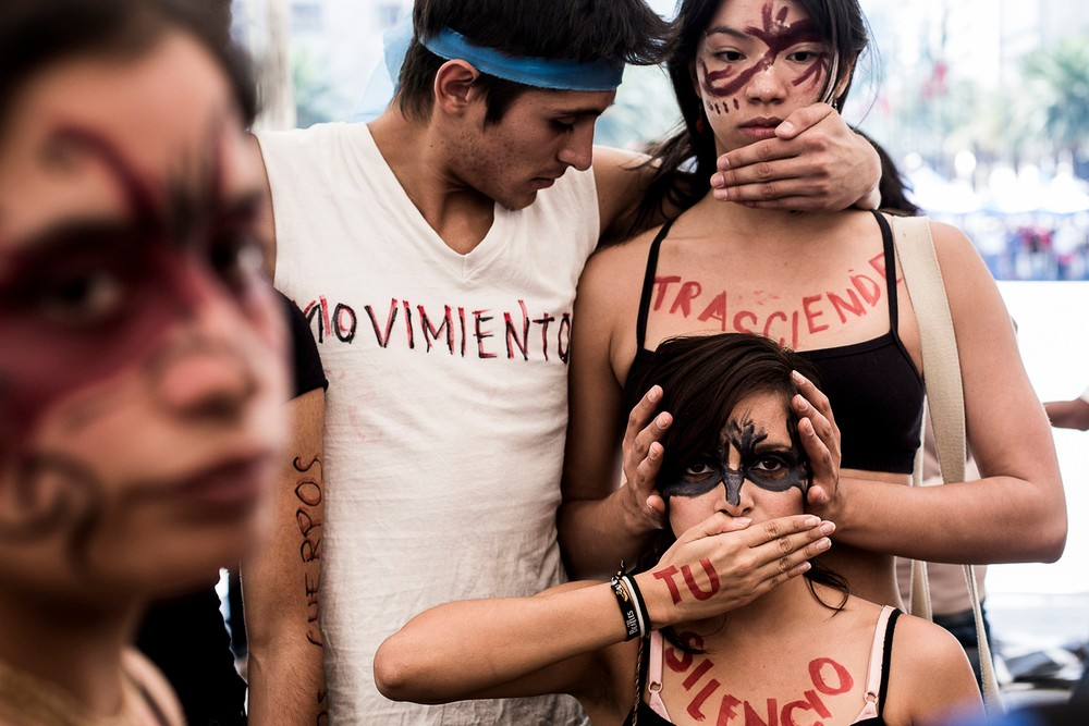 """A dance troop practices wearing body pant that says out, """"Our movement transcends your silence."""""""