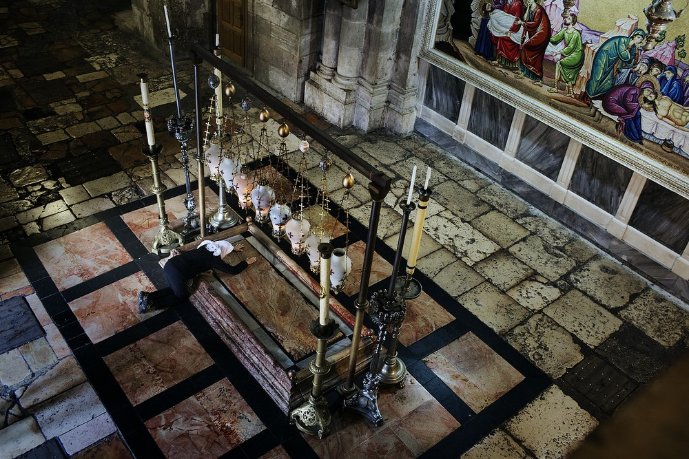 O creștină se roagă pe Piatra Miruirii din Biserica Sfântului Mormânt.