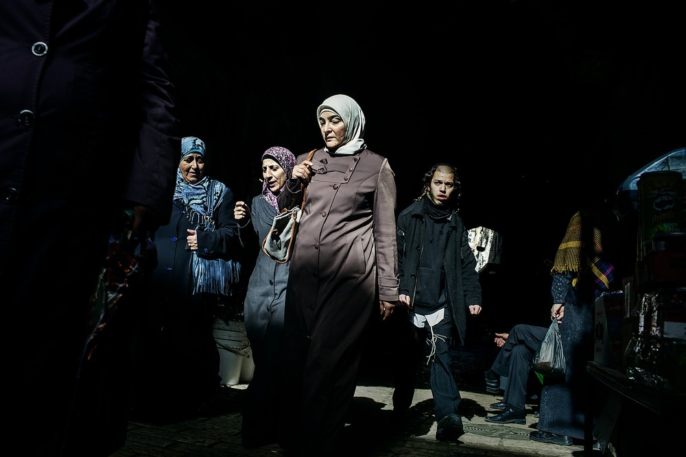Niște femei palestiniene se plimbă pe Via Dolorosa din Orașul Vechi al Ierusalimului