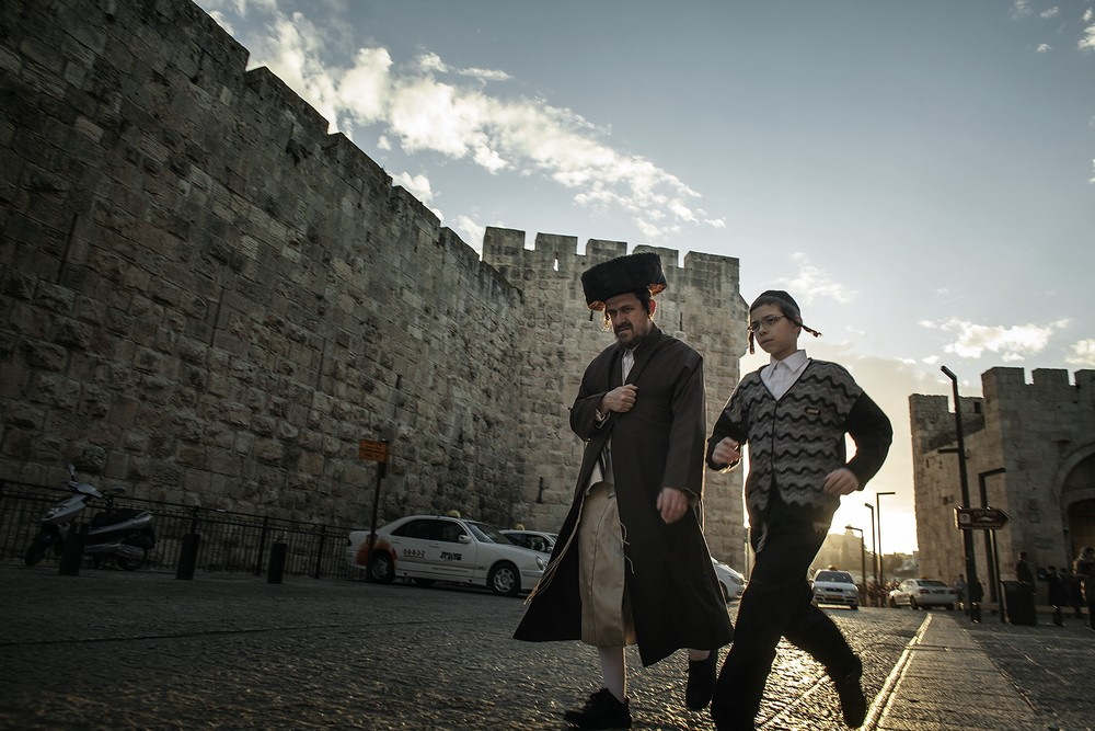 Evrei ultraortodocși trec pe lângă Poarta Jaffa din Orașul Vechi al Ierusalimului.