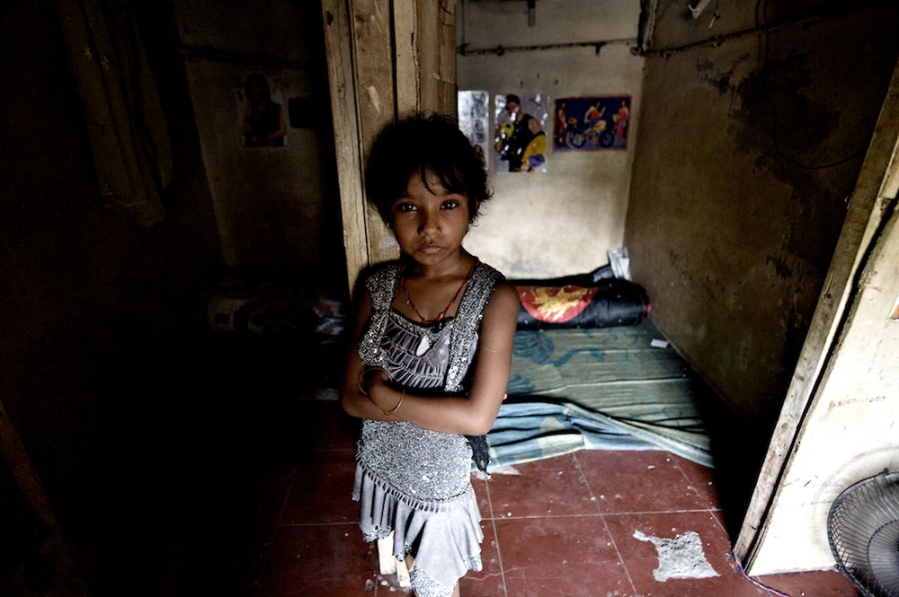 Seven year old Laxmi stands in front of the room she shares with her mother Sangita in a brothel on Hauman Galli. The room is also her mother's place of work.