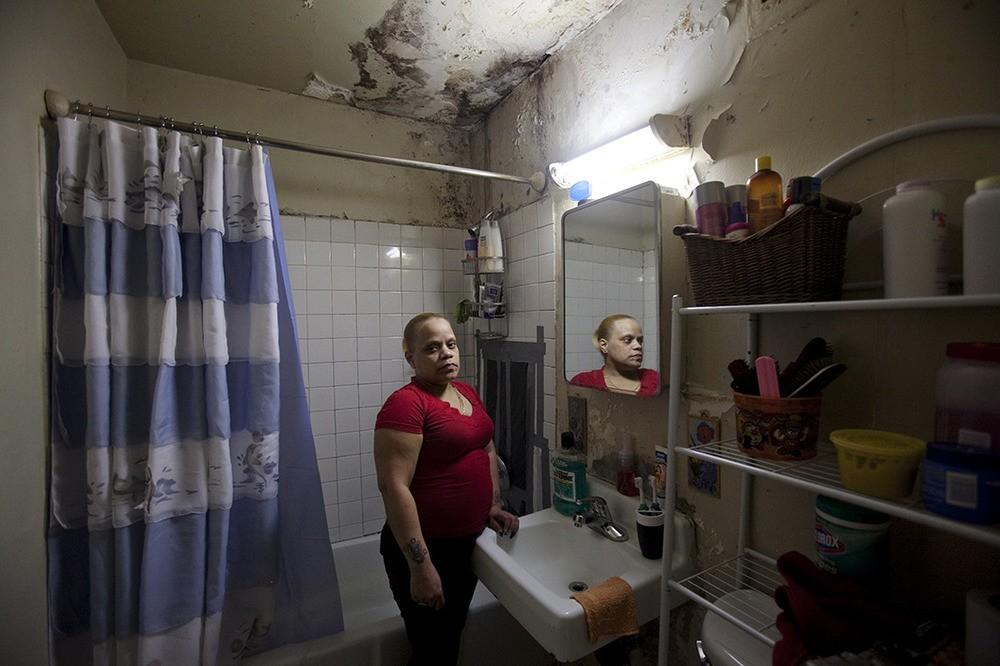 Maribette Cortes en drie andere leden van het gezin lijden aan astma. Ze hebben schimmel in hun badkamer. Melrose Houses, Bronx, NY, 2012.