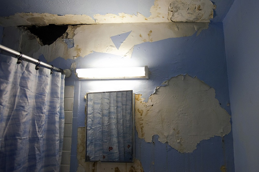 De badkamer van Alicia Moore. Ze wacht al drie jaar tot de NYCHA het gat in haar badkamer komt maken. Melrose Houses, Bronx, NY, 2012.