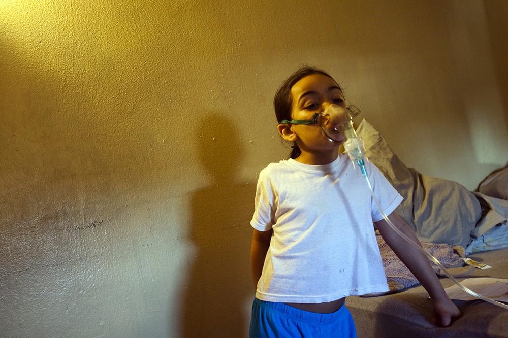 Tristen Davquez woont in een huis waarin ze wordt blootgesteld aan schimmel en kakkerlakken. Ze kreeg de diagnose astma en moet deze machine elke dag gebruiken. Bronx, NY, 2012.