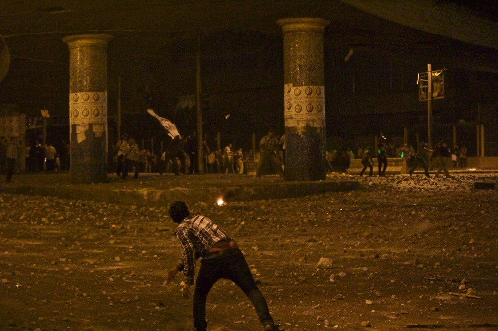 A man throws a rock at supporters of former President Morsi below the 6 October Bridge.