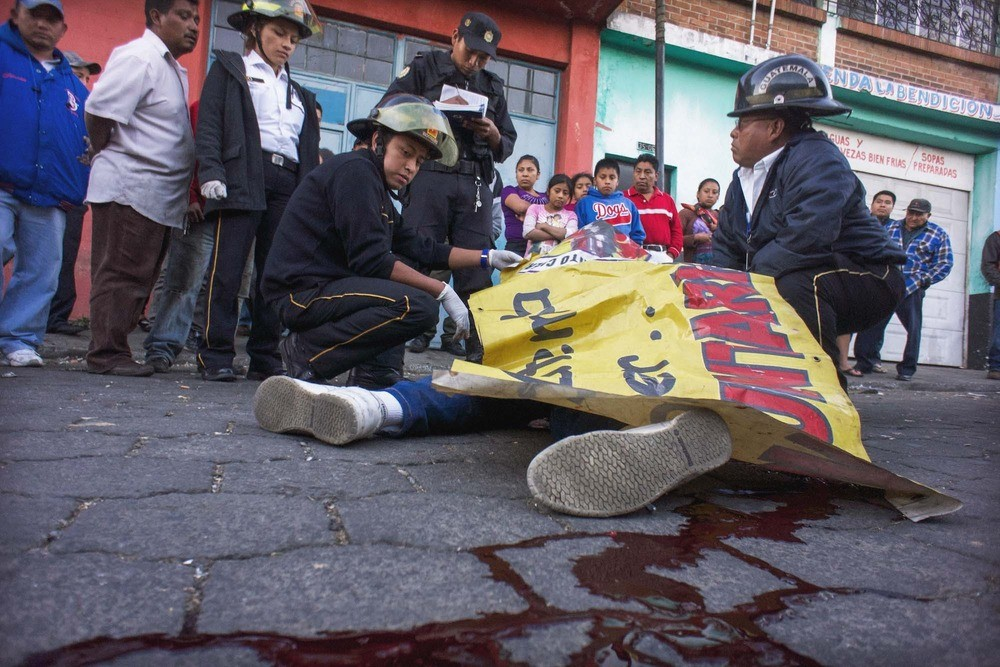 Volunteer medics inspect a dead body at a murder scene in Guatemala City.