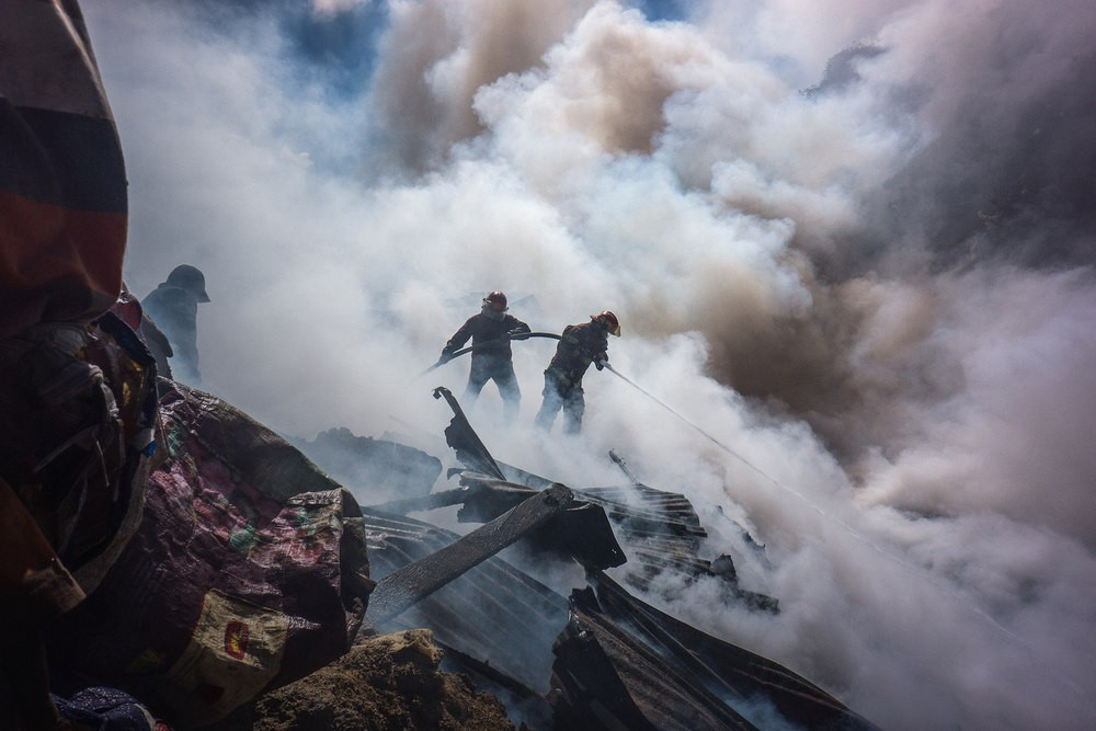 Volunteer firefighters battle a blaze in Guatemala City's dump.