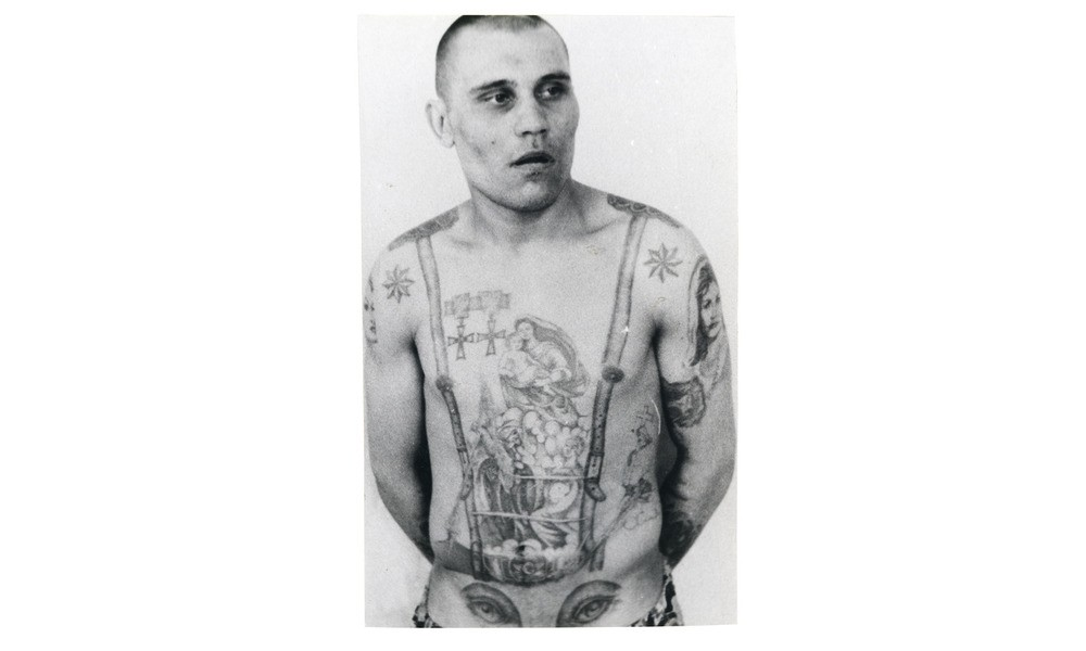"The eight-pointed stars on this inmate's shoulders indicate that he's a criminal ""authority"", while the medals are awards that represent defiance against the Soviet regime. The eyes on the stomach suggest that he's gay (the penis makes the nose of the face)."