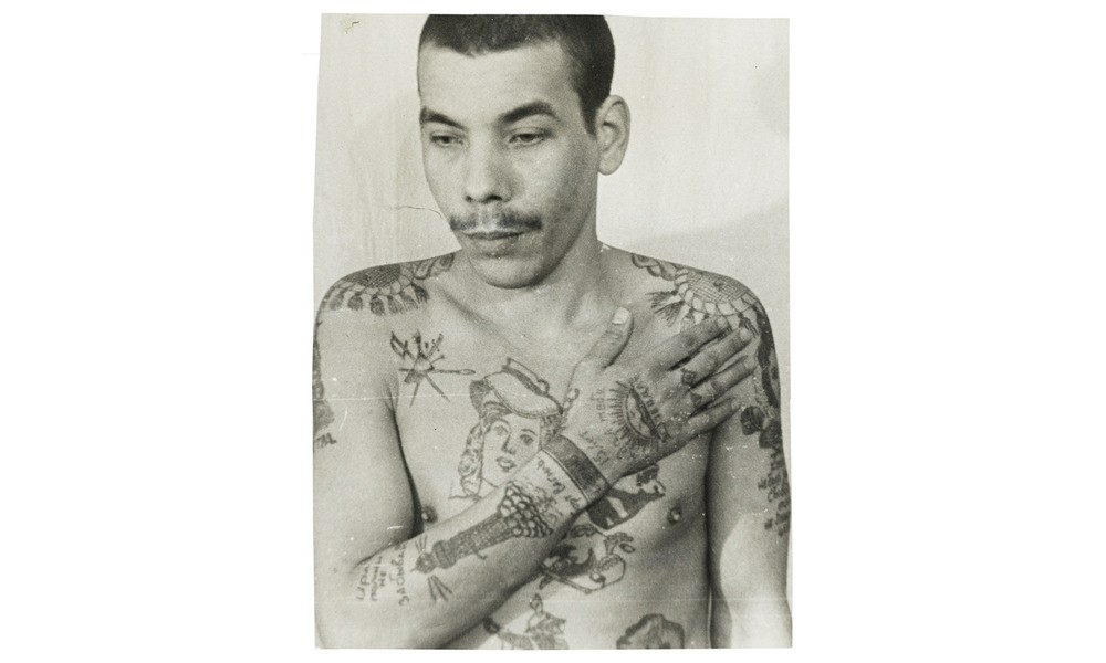 This inmate is not an authoritative thief, but has tried to imitate them with his tattoos to increase his standing within the prison. The lighthouse on his right arm denotes a pursuit of freedom. Each wrist manacle indicates a sentence of more than five years.