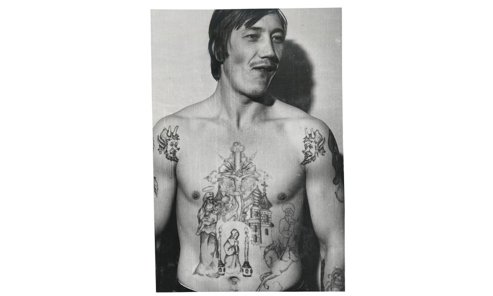 The devils on this inmate's shoulders symbolize a hatred of authority and the prison structure. This type of tattoo is known as an oskal (grin), a baring of teeth towards the system.