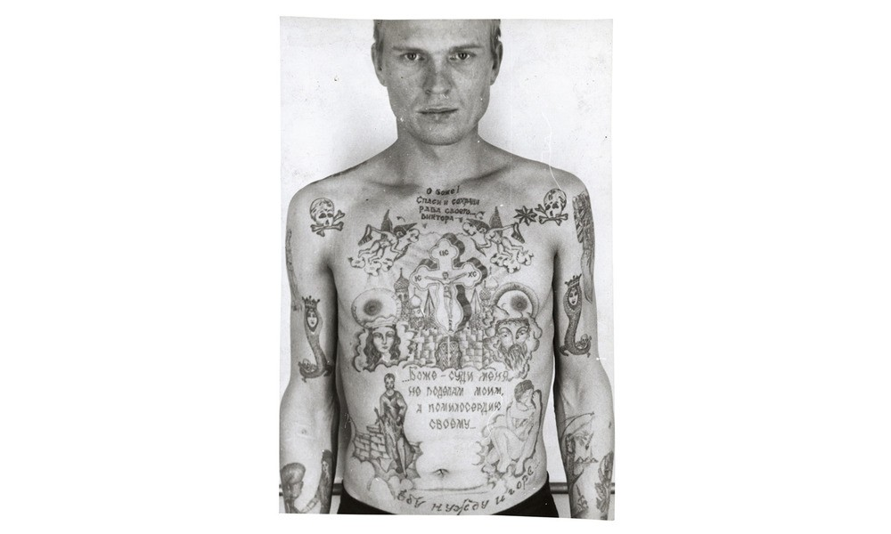 "The skull and crossbones on the prisoner's shoulders indicate that he's serving a life sentence, and the tattoo of the girl ""catching"" her dress with a fishing line on his left forearm is one commonly inked onto rapists."
