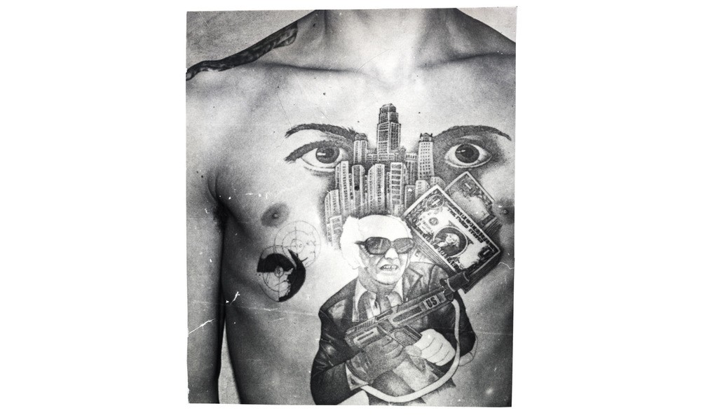The dollar bills, skyscrapers, and machine gun with the initials US stamped on it convey this inmate's love for the American mafia-like lifestyle. The eyes represent the phrase, I'm watching over you (the other inmates in the prison or camp).