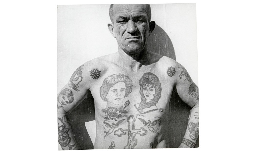 "The rose on this man's chest means that he turned 18 while in prison. The acronym ""SOS"" on his right forearm could stands for ""Spasi, Otets, Syna"" (Save me, father, your son) or Suki Otnyali Svobodu (Bitches robbed my freedom)."