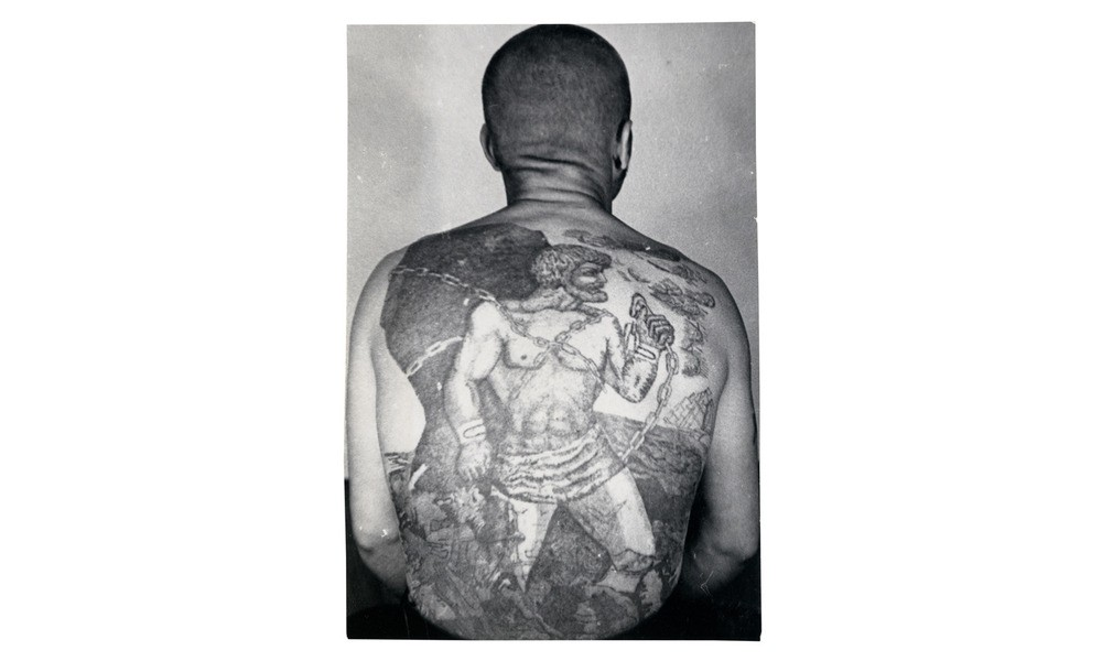 This tattoo is a variation on the myth of Prometheus, who, after tricking Zeus, was chained to a rock in eternal punishment. The sailing ship with white sails means the bearer does not engage in normal work; that he is a traveling thief who is prone to escape attempts.