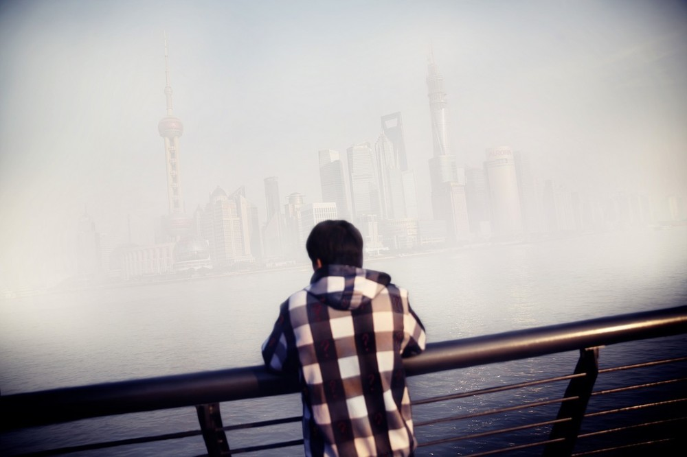 A man looks out at the Shanghai business district