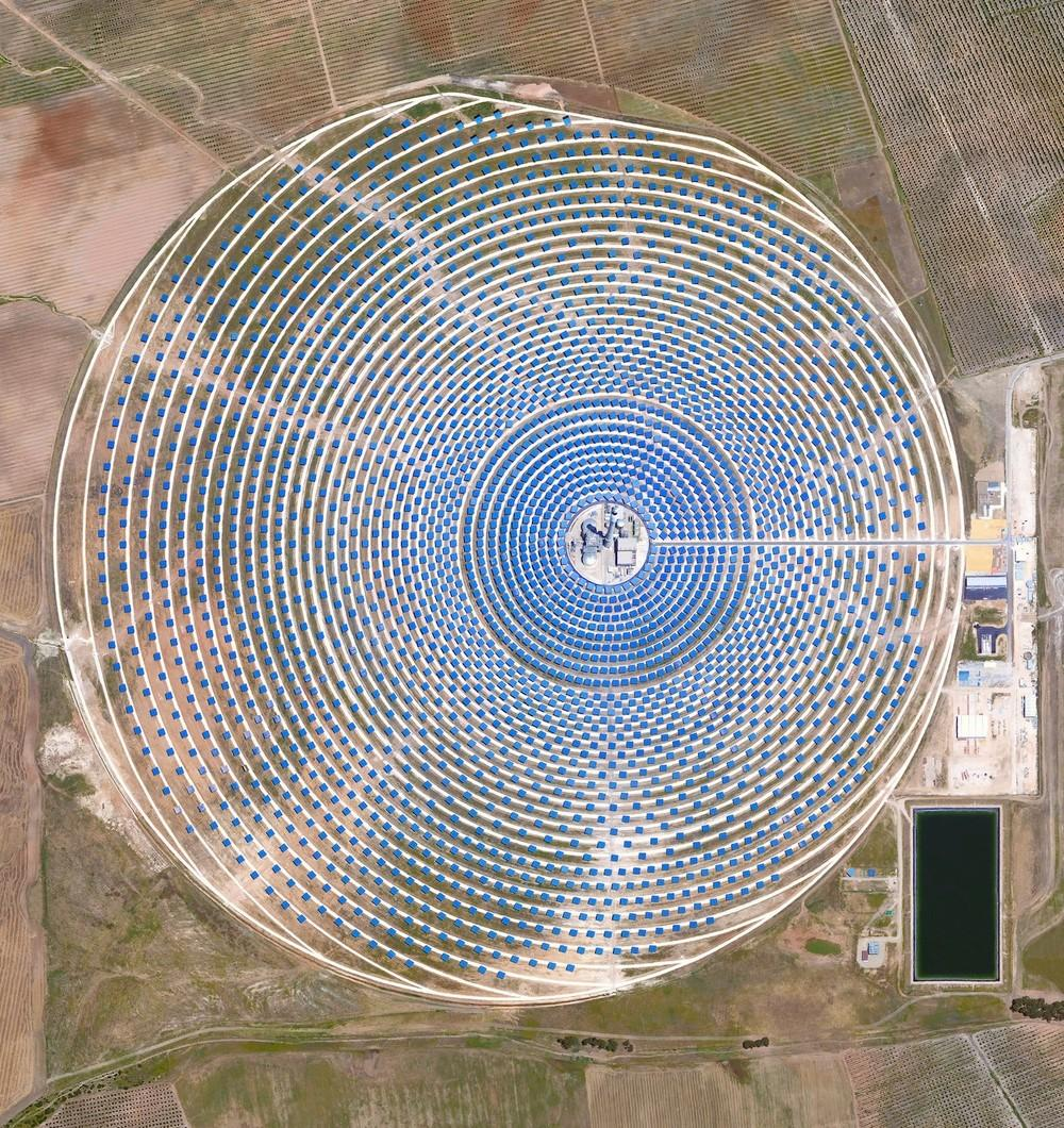 This Overview captures the Gemasolar Thermosolar plant in Seville, Spain. The solar concentrator contains 2,650 heliostat mirrors that focus the sun's thermal energy to heat molten salt flowing through a 140-metre (460-foot) central tower. The molten salt then circulates from the tower to a storage tank, where it is used to produce steam and generate electricity. In total, the facility displaces approximately 30,000 tonnes of carbon dioxide emissions every year.