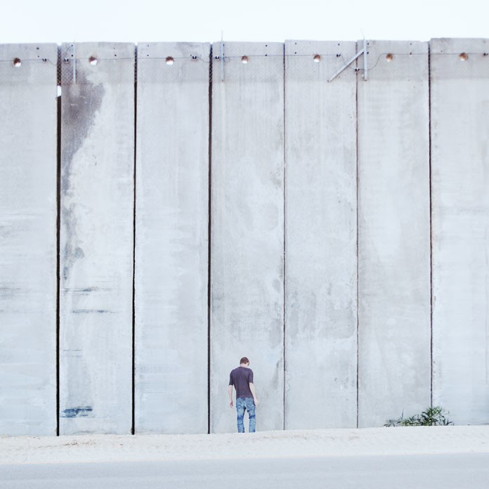 A young man stands at the Israeli side of the wall surrounding Gaza, 2010.