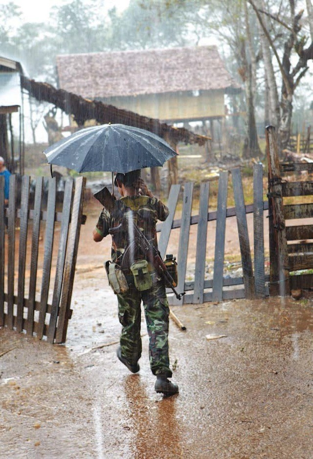 Un soldat merge prin ploaia torenţială în satul Maw Kee.