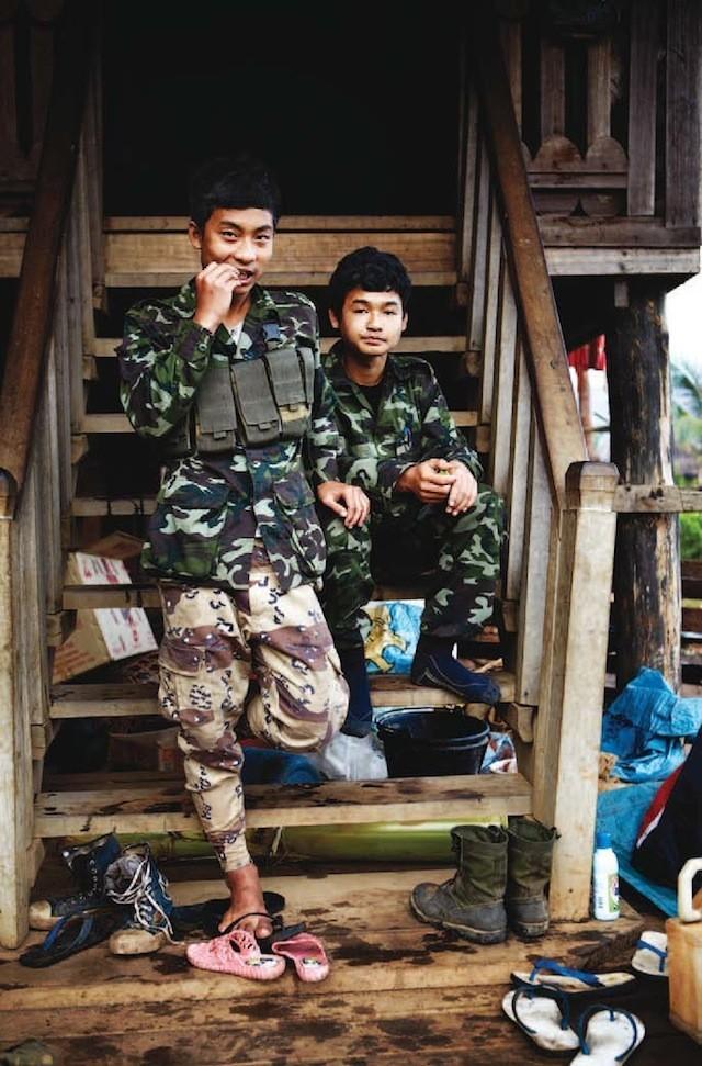 Doi soldați tineri se relaxează, în timp ce așteaptă ordine.