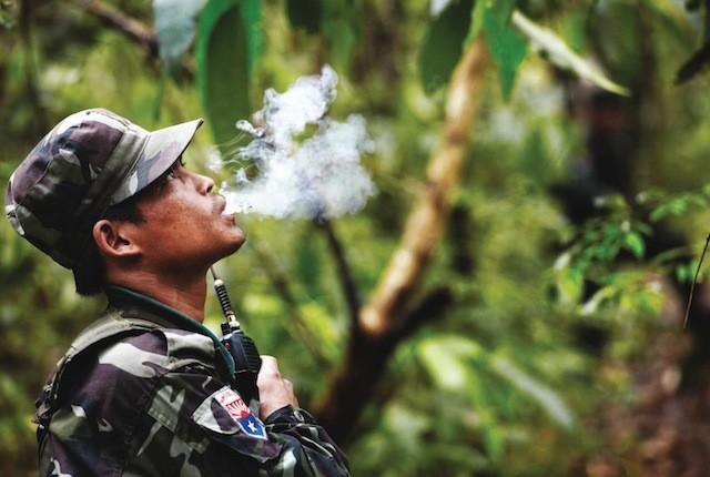 Un soldado se toma un descanso para fumar un cigarrillo durante una caminata hacia una cascada que únicamente han visto 8 extranjeros, según el coronel Ner Dah Mya. Sí, fue así de concreto.