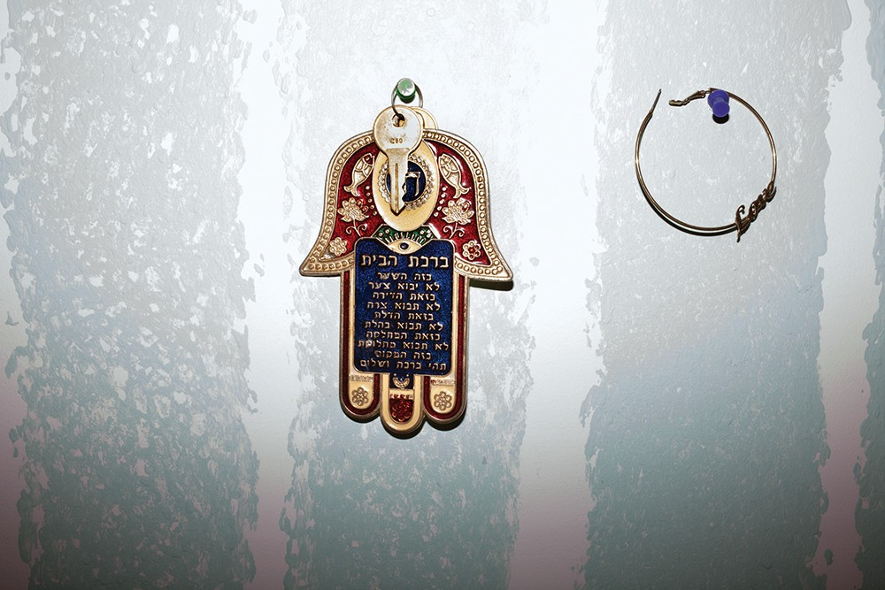 A hamsa, a Middle Eastern symbol used to defend against the evil eye, hangs on Jack's wall.