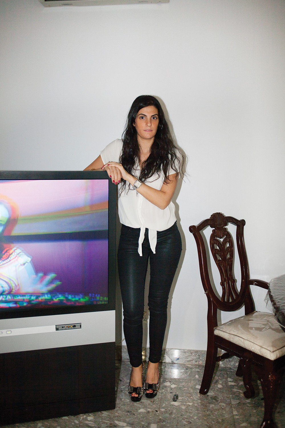 Linda poses next to the family TV, which played Arabic programing throughout the entire shoot.