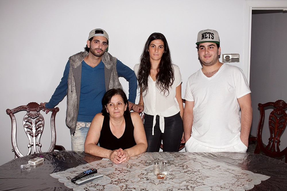"Jack, Mari, Linda, and Etsik at their dining-room table, which is covered in plastic. ""Thank God we're here, and not there,"" said Mari about the uprising in Syria."