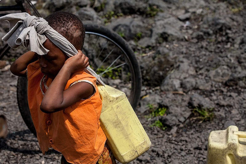 A girl carries waterfrom Lake Kivu in Goma on 22 November 2012. Water supplies were cut as rebels entered Goma on November 20, 2012, forcing residents to draw water from the lake.
