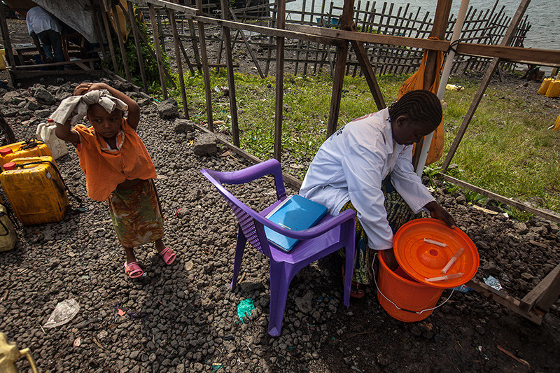 A woman fills a syringe of chlorine, used to sterilize water drawn from Lake Kivu in Goma on November 22, 2012. Water supplies were cut as rebels entered Goma on November 20, 2012.