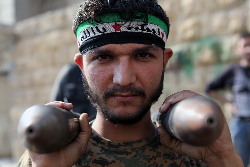 November 21, 2012 – Aleppo, Syria: A fighter with the Free Syrian Army carries homemade rockets to the front line, where fighters with the Free Syrian Army battle  soldiers loyal to Bashar al-Assad for control of Syria's largest city.
