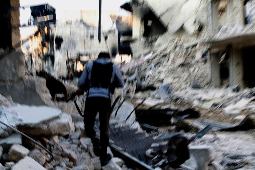 November 21, 2012 – Aleppo, Syria: A fighter with the Free Syrian Army walks toward the front line in the destroyed neighborhood of Karm al-Jabal. This area has seen some of the heaviest fighting in Aleppo.