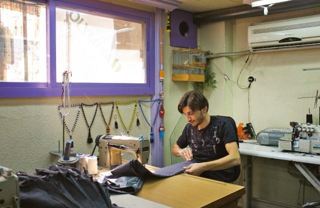 Un tailleur d'Al-Salihiyah coud les jambes de pantalons d'uniformes scolaires. Avec la montée de la violence, beaucoup d'écoles ont assoupli leur code vestimentaire.