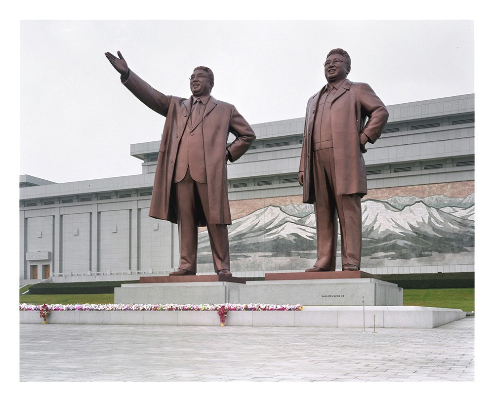 Mansudae Grand Monument with Kim Il Sung and Kim Jong Il's 20 meters tall statues in front of the sacred Mount Paektu's 70 meter long mosaic.