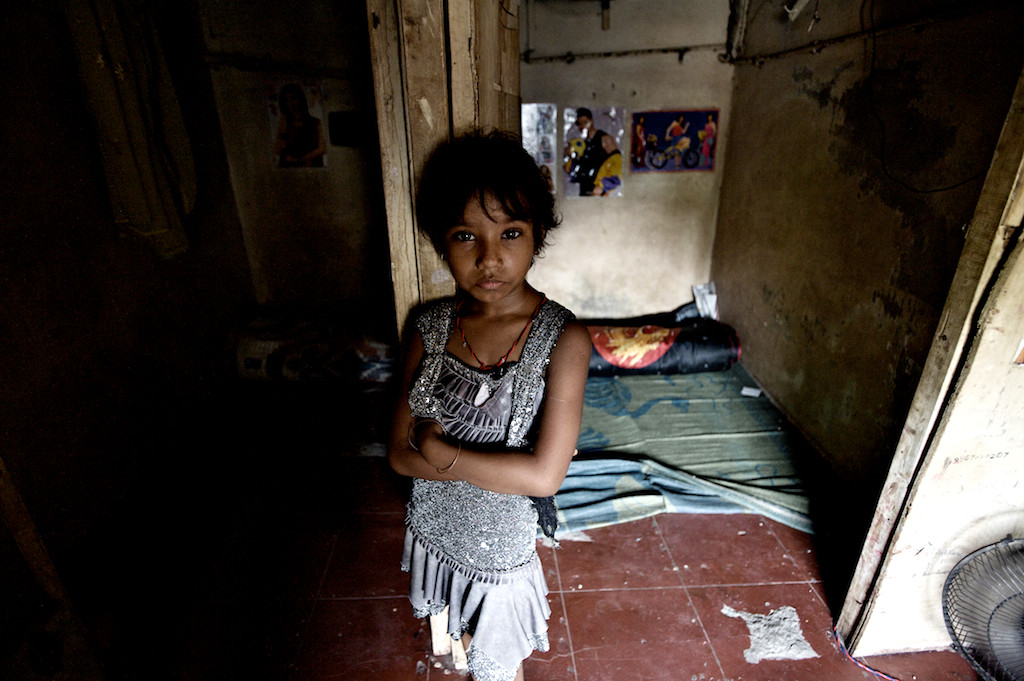 Seven-year-old Laxmi stands in front of the room she shares with her mother Sangita in a brothel on Hauman Galli. The room is also her mother's place of work.