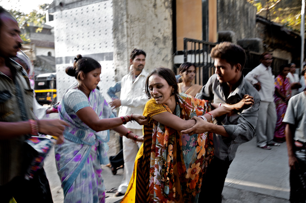 Family members have to hold Durga, 23, Mumtaz's eldest daughter back as she tries to throw herself upon her mother's body. Durga is a widow and has two children of her own.