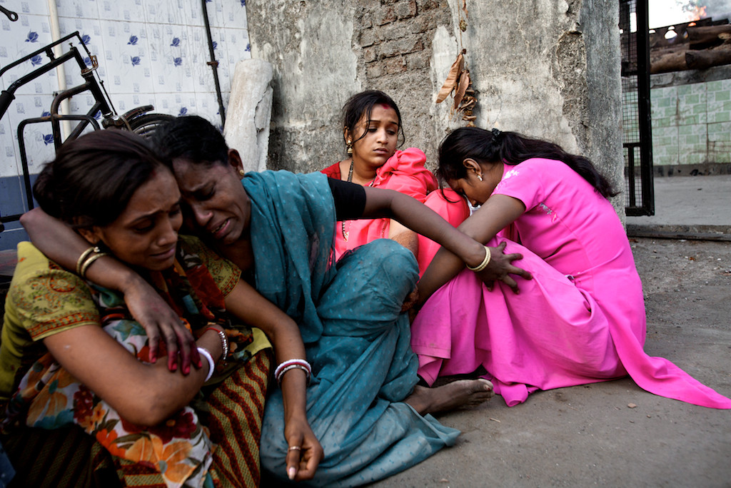 Mumtaz's sister and eldest daughters wait outside the funeral ground while her body is cremated. Her 18-year-old daughter was getting married as her mother was admitted to hospital.