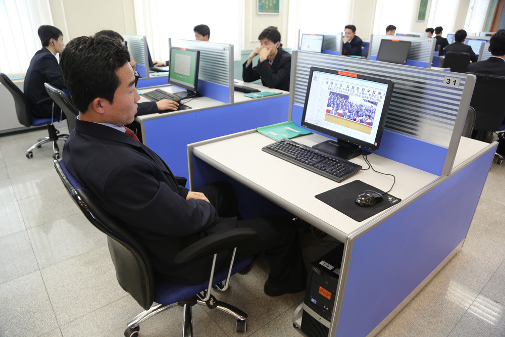 A student in the Kim Il Sung University computer lab looks at headlines about the basketball game in the state paper.