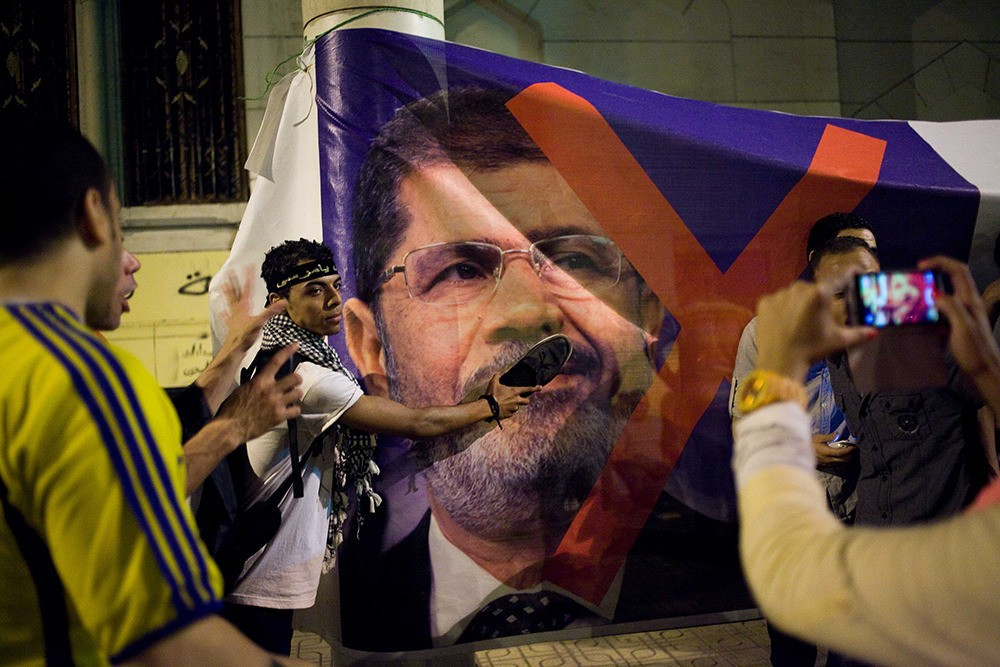 A young Egyptian protester takes off his shoe, placing it into a Morsi poster, a serious sign of disrespect in Egypt.